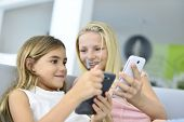 Young girls playing together with smartphone