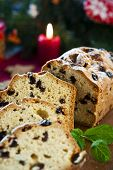 Sliced Fruitcake With Raisins And Mint Leaf On Christmas Background