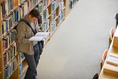 Student reading a book from shelf standing in library at the university