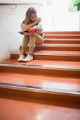 Upset student sitting on stairs in college