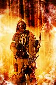 stock photo of chemical weapon  - Soldier with a bow in a forest on fire