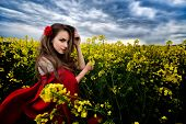 stock photo of cloak  - beautiful woman with red cloak on blooming rapeseed field in summer - JPG
