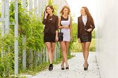 Three important and successful business woman walking down the street