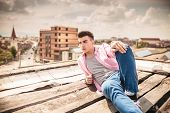 side view of a relaxed young man lying on the roof top of a building with city in the background