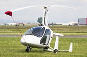 stock photo of rotor plane  - White gyro plane with two seats, stationed on an airfield