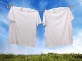 White t-shirt hanging on outdoor clothesline with blank front ready for logo or message
