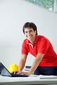 Portrait of young male architect in casual wear smiling while working on laptop