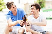 Two young men having beer together