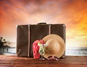 Concept of summer travelling with old suitcase and accessories. Blur beach on background