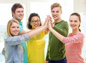 education and friendship concept - five smiling students giving high five at school