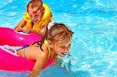 Children wearing life jacket in swimming pool.