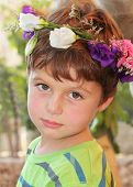 Birthday boy in a beautiful park. The boy wore a wreath of flowers