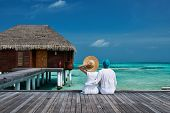 pic of couple sitting beach  - Couple on a tropical beach jetty at Maldives - JPG