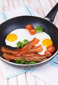 stock photo of scrambled eggs  - Scrambled eggs and bacon on frying pan on table close - JPG