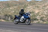 image of crotch-rocket  - Speeding motorcycle racing around a corner on a country back road - JPG