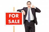 Male realtor standing by a for sale sign isolated on white background