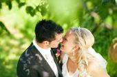 stock photo of wedding couple  - wedding couple hugging and kissing in a private moment of joy - JPG