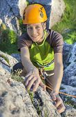 Smiling Woman, Rock Climber In Yellow Helmet Reaching Top Of Mountain During Sunset.