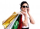 Portrait of smiling woman in glasses with shopping bags talking on the mobile phone - isolated on white.