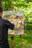 An artist is painting an abstract picture