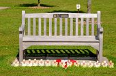 Wooden bench with poppies and crosses.