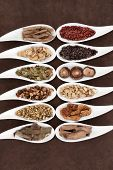 Yang herbs used in chinese herbal medicine in white china dishes over lokta paper background.