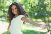 Young girl smiling at the camera with arms outstretched on a sunny day