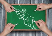 Composite image of multiple hands drawing handshake with chalk on wooden board