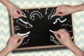 Composite image of multiple hands drawing arrows with chalk against blackboard