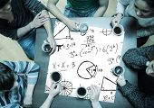 People sitting around table drinking coffee with page showing math equations
