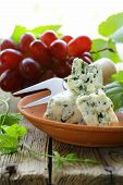 pieces of blue cheese with red grapes on a wooden table