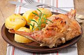 Oven Baked rabbit legs with potatoes and rosemary