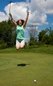 image of ladies golf  - Woman jumps for joy as the ball heads into the cup on the golf green - JPG