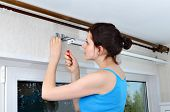 Girl Hangs Vertical Blinds, Tighten With A Screwdriver, Screw Brackets
