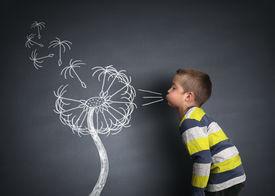 foto of dandelion seed  - Child blowing dandelion seeds on a blackboard concept for wishing - JPG