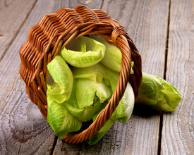 picture of endive  - Wicker Basket with Fresh Crunchy Endive Leaves closeup on Rustic Wooden background - JPG