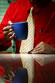 Man wearing red long sleeve shirt, yellow necktie and holding a coffee mug