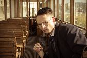 Man With Glasses In A Suit Sitting In An Old Wooden Wagon Train And Smoking