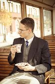 Man With Glasses On Train Drinking Coffee Or Tea