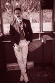 Man With Mustache In Suit Posing In A Wagon Train Or Tram