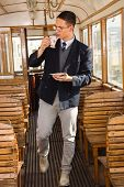 Standing Man With Mustache And Glasses On Train Wooden Wagon Drinking Coffee Or Tea From Cup And Loo