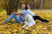 Young Couple With A Dog In The Autumn Forest