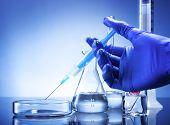Laboratory equipment syringe in hand glass bowl