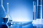 Laboratory equipment bottles flasks on blue background