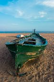 Green Fishing Boat On The Beach And Blue Sky