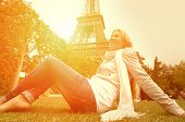Happiness Woman seating on the grass in Paris under sunlight