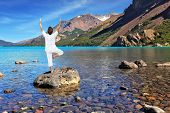Yoga on the lake. Mature woman in white performs asana