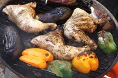 fresh group of grilled chicken thighs with green orange yellow pepper bell slice and eggplants on hot grill bbq high resolution