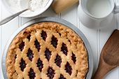 High angle shot of a fresh baked fruit pie with a lattice crust. the pie is surrounded by baking items. Horizontal format.