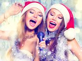 Christmas party, karaoke. Beauty girls in santa hat with a microphone singing and dancing over holiday blinking background. Disco. New year celebration
